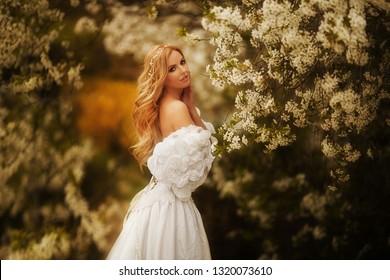beautiful tender girl in a white dress walks in the spring garden