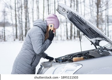 A beautiful tense woman stands on the road and waits for help next to a broken car with the hood open