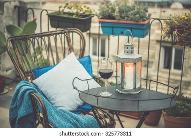 Beautiful terrace or balcony with cozy rattan armchair and wine glass on small iron table. Toned picture