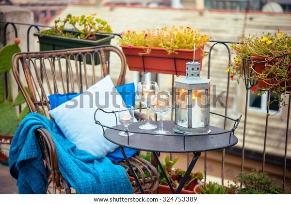 Beautiful terrace or balcony with cozy rattan armchair and candles on small iron table
