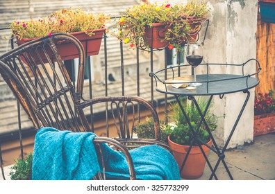 Beautiful terrace or balcony with small iron table, chair and wine glass. Toned image