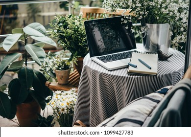 Beautiful terrace or balcony with small table, laptop and flowers