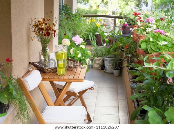 Красивая терраса или балкон с небольшим столом, стулом и цветами. Летнее время Идиллические сидения на террасе с напитком.