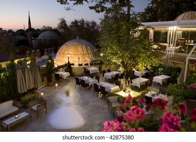 A beautiful terrace with a panoramic view of some mosques and minaret, where a dervish is whirling