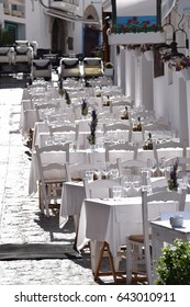 Beautiful terrace of a restaurant in a mediterranean village in the sunlight - all decorated in white - tables and chairs on the cobbled pavement