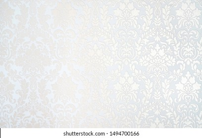 Beautiful texture of paper Wallpaper embossed in form of a classic floral ornament in light golden beige and white tones.