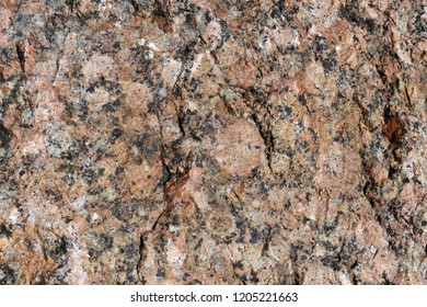 Beautiful texture of red and black surface of a shiny rock. An interesting natural texture that can be used for example as a background or wallpaper.