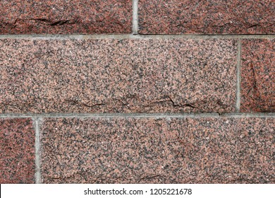 Beautiful texture of red and black surface of a brick wall with horizontal lines. An interesting natural texture that can be used for example as a background or wallpaper.
