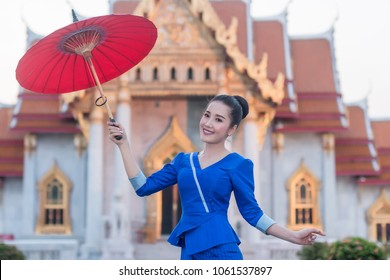 Beautiful Thai girl in Thai costume with umbrella,Asian woman wearing traditional Thai culture standing in front at temple.