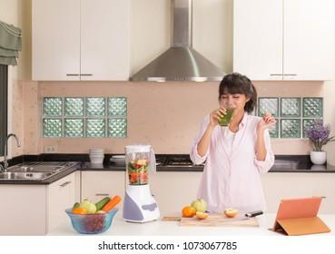 Beautiful Thai girl drinking fruit juice in modern style kitchen