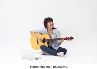 Beautiful Thai girl learning to play guitar online sitting on white background
