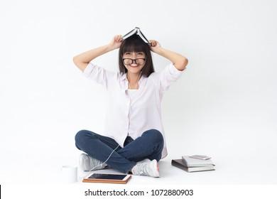 Beautiful Thai girl learning and study hard sitting on white background