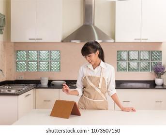 Beautiful Thai girl preparing to shopping household stuff online in modern style kitchen