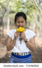 Beautiful Thai girl in Thai traditional costume is smelling flower