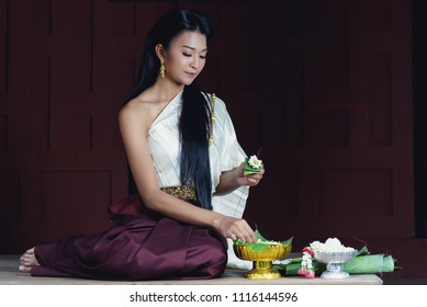 Beautiful Thai girl in traditional costume,making a Thai garland at traditional Thai wooden house