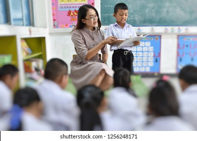 Beautiful Thai teacher is teaching many elementary school students in the classroom, One male student is leading his friends to read books simultaneously.