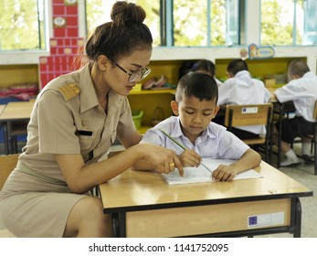 Beautiful Thai teachers are teaching one-on-one to little boy students.