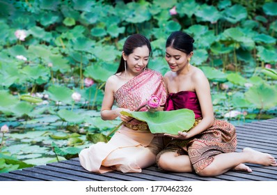 Beautiful Thai two women in thai traditional costume trying to roll up lotus flower while sitting on wooden path outdoors at lotus pond background. Asia young woman wearing Thailand traditional dress.