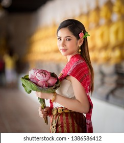 Beautiful Thai woman holding pink lotus and pray for Buddha with Thai tradition costume in ancient temple at Ayutthaya province, Thailand.