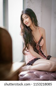 beautiful Thai woman in sexy pink lingerie .  she smile on the red sofa