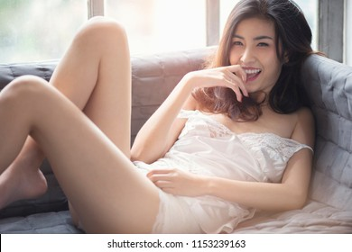 beautiful Thai woman in sexy white lingerie .  she smile on the gray sofa
