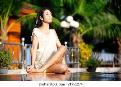 Beautiful Thai woman sitting crossed leg in meditation at health resort