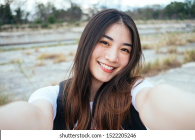 Beautiful thai woman taking selfie with cute smile.