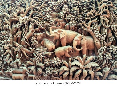 Beautiful Thailand Antique Art Handmade Furniture. Carvings Elephant Family in The Wood on The Wooden Frame used as Antique Design Interior Furniture Hanging on the Wall for Vintage Retro Style Room.