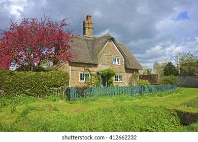 A beautiful thatched country cottage in the heart of the Cotswolds under a stormy spring sky, Gloucestershire, England, UK