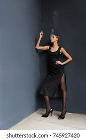 A beautiful thin blonde woman in a black dress and black pantyhose and shoes smokes on a background of a dark blue wall