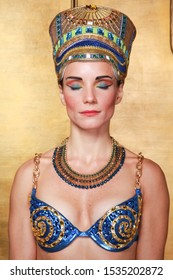 Beautiful thin Egyptian woman with pronounced cheekbones in a huge gold headdress without hair in a blue swimsuit on the background in the Studio.