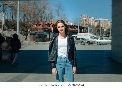 beautiful thin fashion girl stands in the middle of the street. There is a girl with a stroller in the background
