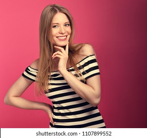 Beautiful thinking wide toothy smiling blond woman in striped dress posing on pink background. Closeup toned portrait