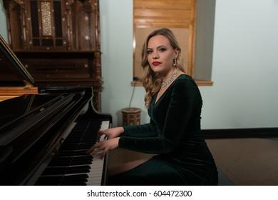 Beautiful Thoughtful Girl Sitting Near Piano - Fashion Studio Portrait
