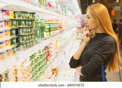 Beautiful thoughtful young woman choosing food at the supermarket standing in front of the refrigerator copyspace choice deciding decision thinking people lifestyle consumerism lifestyle shopping