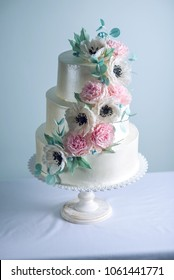 Beautiful three tiered white wedding cake decorated with flowers sugar pink peonies and green leaves on the table. The concept of elegant holiday desserts