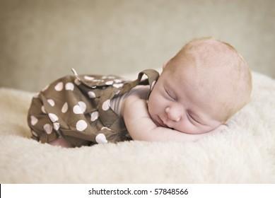 A beautiful three week old baby girl sleeping, soft focus