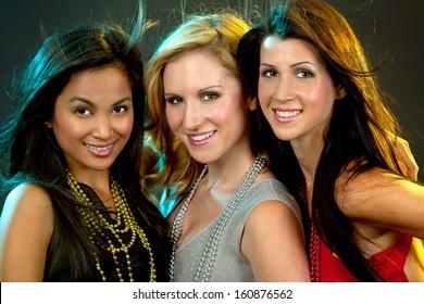 beautiful three women having fun during party on dark background