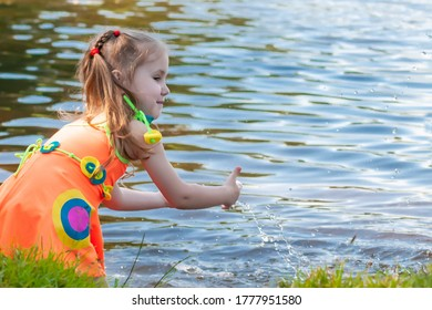 beautiful three year old girl swimming with her mother in a lake on a clear summer day