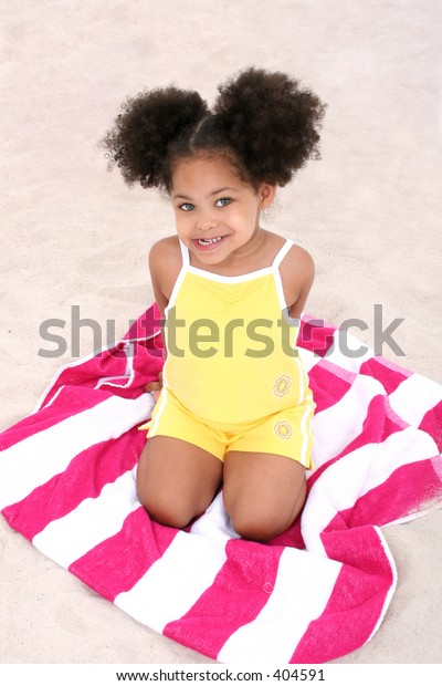 Beautiful Three Year Old Girl Sitting On Beach Towel In The Sand.  Beautiful eyes.