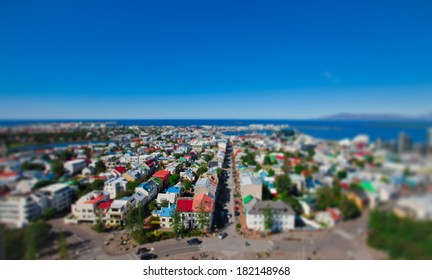 Beautiful TILT-SHIFT super wide-angle aerial view of Reykjavik, Iceland with harbor and skyline mountains and scenery beyond the city, seen from the observation tower of Hallgrimskirkja Cathedral.