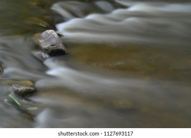 Beautiful time exposure of moving water through some rocks on a ledge.