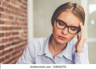 Beautiful tired business woman is touching her forehead while sitting with closed eyes in office