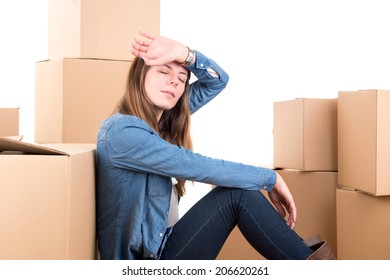 Beautiful tired girl with cardboard boxes unpacking in new home