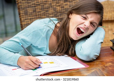 beautiful tired girl student doing her homework while yawning