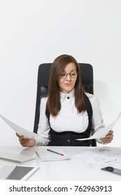 The beautiful tired perplexed and stress brown-hair business woman in suit and glasses sitting at the desk, working at contemporary computer with documents in light office on white background