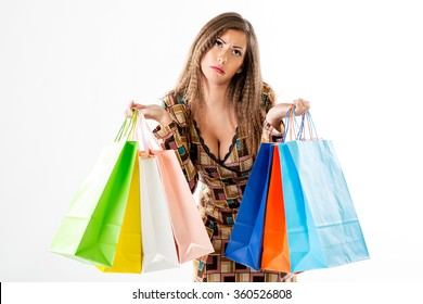 Beautiful tired woman with many multicolored shopping bags. White background.