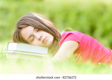 beautiful and tired young student girl lying on green grass, pile of books under her head, her eyes closed. Summer or spring green park in background