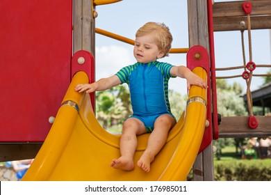 beautiful toddler boy having fun on playground in summer on big construction
