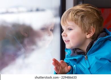 Beau petit garçon regardant par la fenêtre du train, pendant qu'il bouge. En vacances et en train en hiver.